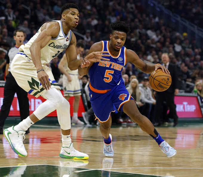 New York Knicks' Dennis Smith Jr. (5) drives against Milwaukee Bucks' Giannis during the first half of an NBA basketball game Monday, Dec. 2, 2019, in Milwaukee. (AP Photo/Jeffrey Phelps)