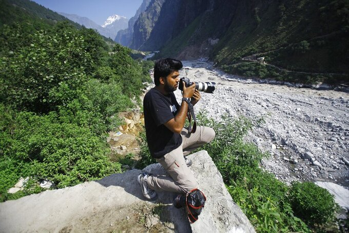 Reuters photographer Danish Siddiqui covers the monsoon floods and landslides in the upper reaches of Govindghat, India, Saturday, June 22, 2013. Afghan government forces battled Friday to retake a border crossing with Pakistan from Taliban insurgents, and the Reuters news agency said one of its photographers was killed in the area. Reuters said Pulitzer Prize-winning photographer Siddiqui, who was embedded with the Afghan special forces, was killed Friday, July 16, 2021, as the commando unit sought to recapture Spin Boldak. (AP Photo/Rafiq Maqbool)