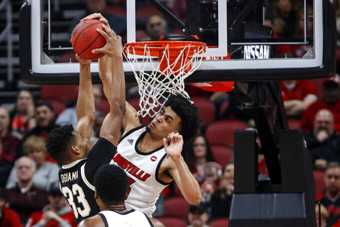 FILE - In this Feb. 5, 2020, file photo, Louisville forward Jordan Nwora (33) blocks the shot of Wake Forest forward Ody Oguama (33) during the first half of an NCAA college basketball game in Louisville, Ky. Nwora was selected to the Associated Press All-ACC team selected Tuesday, March 10, 2020. (AP Photo/Wade Payne, File)
