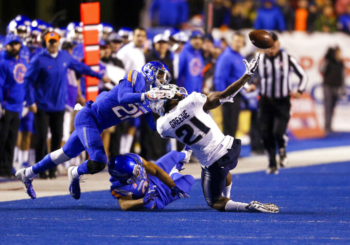 Utah State wide receiver Jalen Greene (21) reaches back for the ball as Boise State safety Tyreque Jones (21) grabs Greene's helmet to break up a reception attempt in the second of an NCAA college football game, Saturday, Nov. 24, 2018, in Boise, Idaho. Boise State won 33-24. (AP Photo/Steve Conner)
