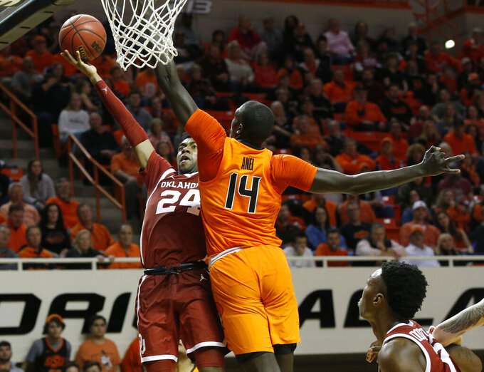 Oklahoma guard Jamal Bieniemy (24) shoots as Oklahoma State forward Yor Anei (14) defends during the second half of an NCAA college basketball game in Stillwater, Okla., Wednesday, Jan. 23, 2019. (AP Photo/Sue Ogrocki)