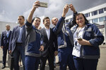 Ukrainian President Volodymyr Zelenskiy, center, poses for a selfies as he visits the