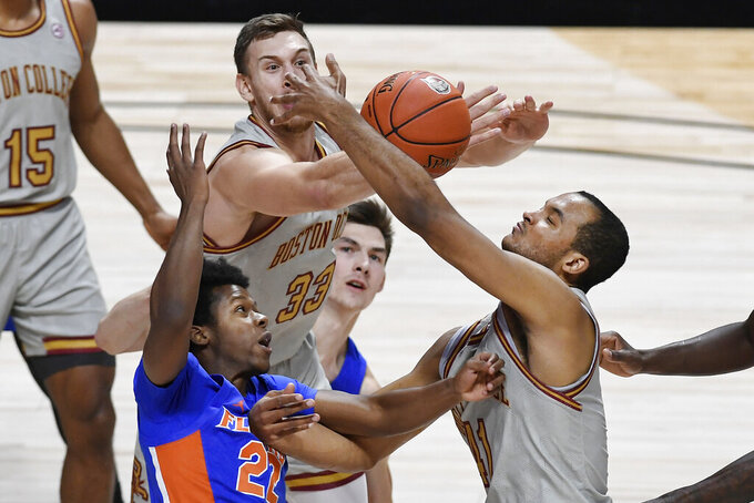 Florida's Tyree Appleby, bottom, tries for a shot as Boston College's James Karnik, top, and Steffon Mitchell, right, defend during the first half of an NCAA college basketball game Thursday, Dec. 3, 2020, in Uncasville, Conn. (AP Photo/Jessica Hill)