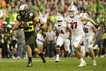 Oregon safety Brady Breeze, left, runs for a touchdown past Wisconsin running back Garrett Groshek after a blocked punt during second half of the Rose Bowl NCAA college football game Wednesday, Jan. 1, 2020, in Pasadena, Calif. (AP Photo/Marcio Jose Sanchez)