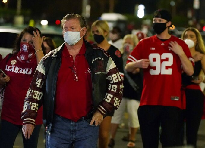 Fans arrive for an NCAA College Football Playoff national championship game between Alabama and Ohio State Monday, Jan. 11, 2021, in Miami Gardens, Fla. (AP Photo/Chris O'Meara)