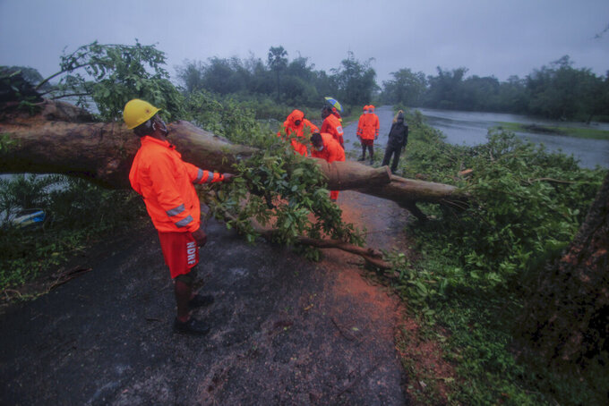 National Disaster Response Force personnel clear trees that got uprooted in rain and strong winds as Cyclone Yaas intensifies over the Bay of Bengal in Balasore district, Odisha, India, Wednesday, May 26, 2021. Heavy rain and a high tide lashed parts of India's eastern coast as the cyclone pushed ashore Wednesday in an area where more than 1.1 million people have evacuated amid a devastating coronavirus surge. (AP Photo)