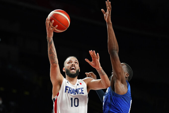 France's Evan Fournier (10) drives to the basket past the United States' Bam Adebayo, right, during a men's basketball preliminary round game at the 2020 Summer Olympics, Sunday, July 25, 2021, in Saitama, Japan. France won 83-76. (AP Photo/Charlie Neibergall)