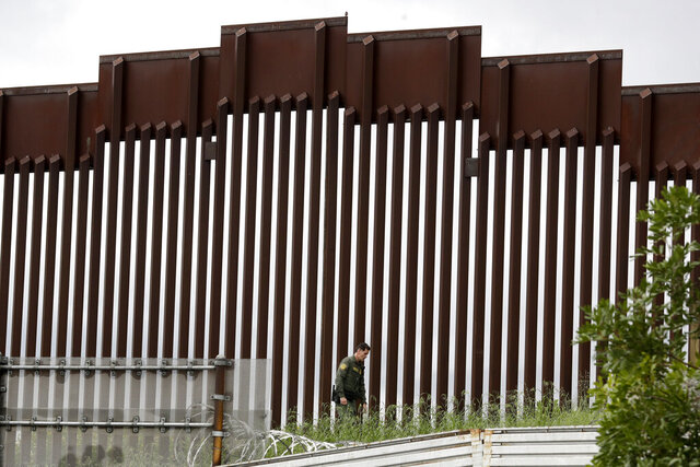 FILE - In this March 18, 2020, file photo, a Border Patrol agent walks along a border wall separating Tijuana, Mexico, from San Diego, in San Diego. U.S. authorities wield extraordinary power available in public health emergencies, like the coronavirus pandemic, to expel Mexicans and many Central Americans immediately to Mexico and waive immigration laws that include rights to seek asylum. (AP Photo/Gregory Bull, File)