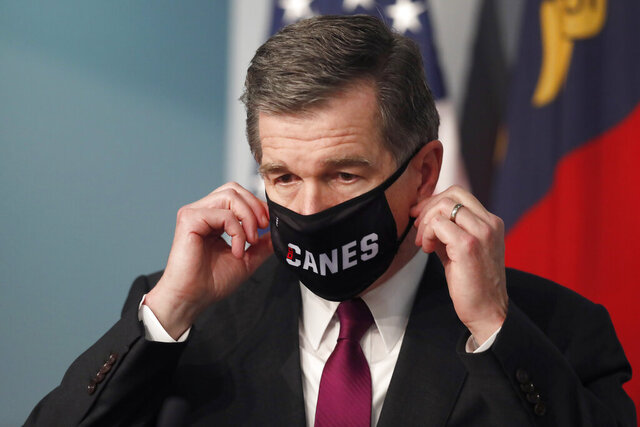 Gov. Roy Cooper prepares to take off his Canes mask before speaking during a briefing at the Emergency Operations Center in Raleigh, N.C., Wednesday, July 1, 2020.  (Ethan Hyman/The News & Observer via AP)