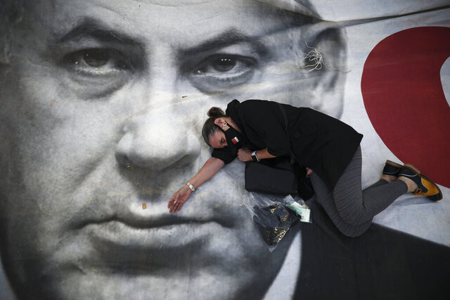 A woman takes part in a protest against Israeli Prime Minister Benjamin Netanyahu, seen on the poster, in Tel Aviv, Israel, Sunday, April 19, 2020. The demonstrators accused Netanyahu of using the coronavirus crisis as cover to undermine the country's democratic institutions. (AP Photo/Oded Balilty)