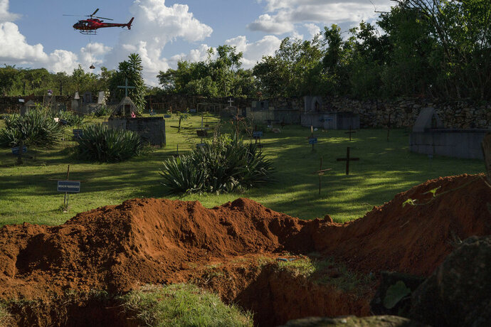 FILE - In this Jan. 28, 2019 file photo, a helicopter carrying a body pulled from the mud, days after a Vale dam collapsed, flies over a cemetery with two open graves in Brumadinho, Brazil. Lax regulations, chronic short staffing and a law that muffled the voices of environmentalists on mining licenses made the collapse all but destined to happen, experts and legislators say. (AP Photo/Leo Correa, File)