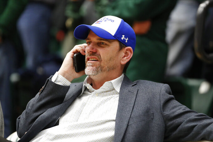 FILE - In this Feb. 6, 2019, file photo, Colorado State football coach Mike Bobo chats on his mobile phone while seated at an NCAA college basketball game between Nevada and Colorado State in Fort Collins, Colo. Bobo preaches toughness and accountability. He demonstrated that toughness last season by walking the sidelined despite fighting a rare autoimmune disease that caused him to lose sensation in both feet. He showed accountability by declining a $100,000 pay increase due to him after the Rams struggled to a 3-9 record in 2018. That's why his messages hit home. (AP Photo/David Zalubowski, File)
