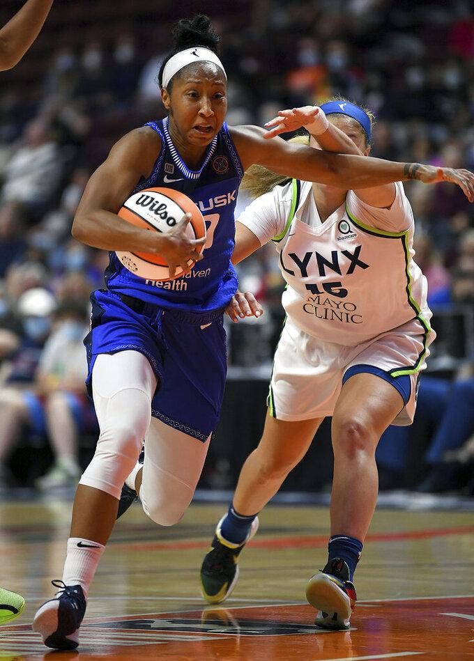 Connecticut Sun's Briann January (20) attempts to move past Minnesota Lynx's Rachel Banham (15) during a WNBA basketball game Tuesday, Aug. 17, 2021, in Uncasville, Conn. (Sarah Gordon/The Day via AP)