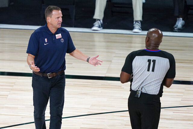 Washington Wizards head coach Scott Brooks talks with referee Derrick Collins (11) during the second half of an NBA basketball game between the Boston Celtics and the Washington Wizards Thursday, Aug. 13, 2020 in Lake Buena Vista, Fla. (AP Photo/Ashley Landis, Pool)