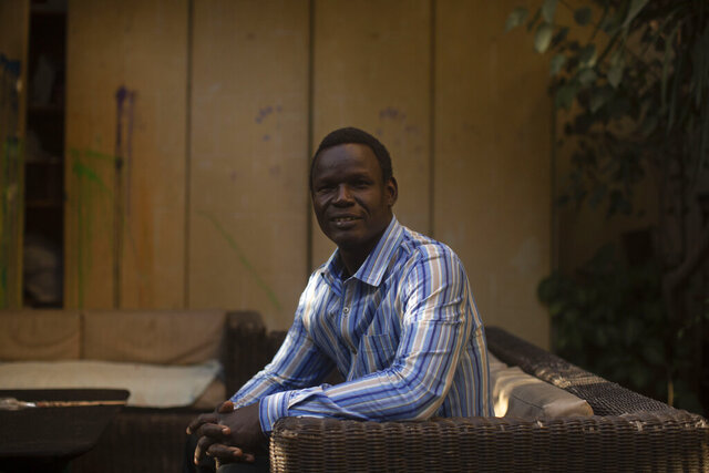 In this Nov. 27, 2019 photo, Patrice Gaudensio, a refugee artist from South Sudan poses for a portrait during an exhibition titled