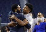 Retired NBA and former Michigan player Jimmy King, left, embraces Jace Howard before Jace's father Juwan is introduced as Michigan's new men's basketball coach, Thursday, May 30, 2019 in Ann Arbor, Mich. (AP Photo/Carlos Osorio)