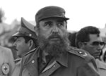 FILE - In this Nov. 2, 1983 file photo, Cuban President Fidel Castro and his brother Raul, head of the Cuban Armed Forces, watch as the first group of Cubans returns home from Grenada, in Havana, Cuba. Raul, who has spent most of his life by the side of his larger-than-life brother, has always seemed more comfortable behind the scenes, chatting and joking with his soldiers rather than giving speeches and posing for photos. (AP Photo/Charles Tasnadi, File)