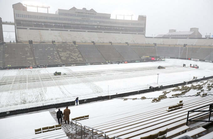 A pair of fans head to their seats in Folsom Field as grounds crew members clear snow from the field before the first half of an NCAA college football game Saturday, Nov. 17, 2018, in Boulder, Colo. (AP Photo/David Zalubowski)