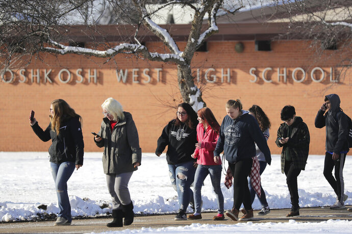 Students are evacuated from the scene of an officer invloved shooting at Oshkosh West High School after an armed student confronted a school resource officer on Tuesday December 3, 2019, at in Oshkosh, Wis. Police in Oshkosh say a police officer and an armed student whom he confronted at the school were both wounded in the confrontation Tuesday morning. (Wm. Glasheen/The Post-Crescent via AP)
