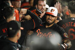 Baltimore Orioles' Anthony Santander, center, is greeted in the dugout by teammates after hitting a three-run home run off Toronto Blue Jays starting pitcher Julian Merryweather during the seventh inning of a baseball game, Friday, Sept. 10, 2021, in Baltimore. (AP Photo/Julio Cortez)