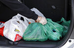A shopper places her goods into her car outside a supermarket in Christchurch, New Zealand, Friday, Aug. 10, 2018. New Zealand plans to ban disposable plastic shopping bags by next July as the nation tries to live up to its clean-and-green image. Prime Minister Jacinda Ardern said Friday that New Zealanders use hundreds of millions of the bags each year and that some of them end up polluting the precious coastal and marine environment. (AP Photo/Mark Baker)