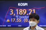 A currency trader walks near a screen showing the Korea Composite Stock Price Index (KOSPI) at the foreign exchange dealing room of the KEB Hana Bank headquarters in Seoul, South Korea, Thursday, April 22, 2021. Asian shares were higher on Thursday after a broad advance on Wall Street led by technology companies and banks. (AP Photo/Lee Jin-man)