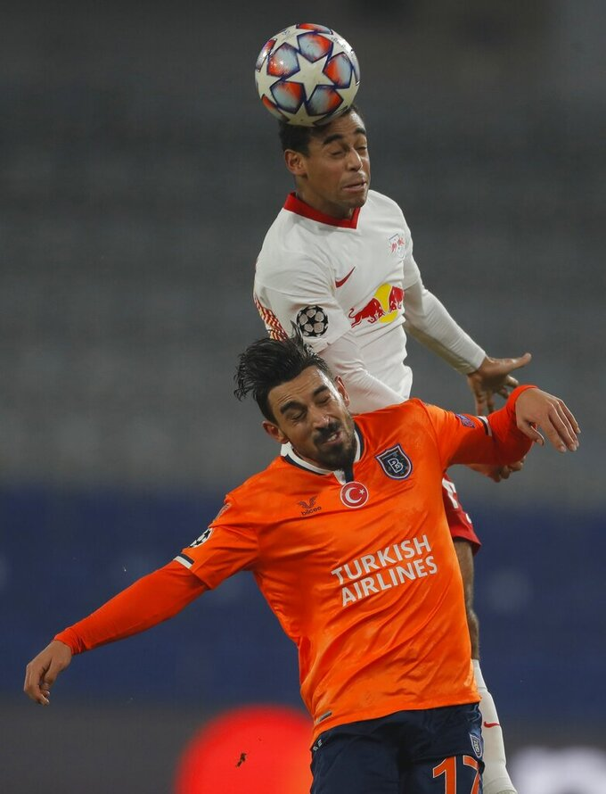 Leipzig's Tyler Adams, background, and Basaksehir's Irfan Can Kahveci jump for the ball during the Champions League group H soccer match between Istanbul Basaksehir and RB Leipzig at Fatih Terim Stadium in Istanbul, Wednesday, Dec. 2, 2020. (AP Photo)