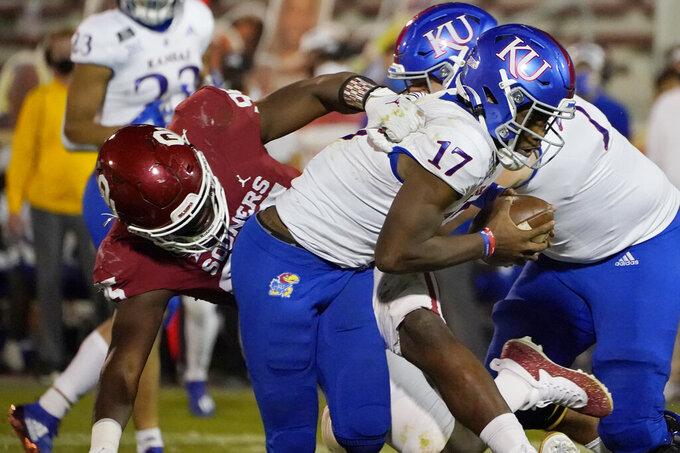 Oklahoma defensive lineman Isaiah Thomas (95) sacks Kansas quarterback Jalon Daniels (17) in the second half of an NCAA college football game in Norman, Okla., Saturday, Nov. 7, 2020. (AP Photo/Sue Ogrocki)