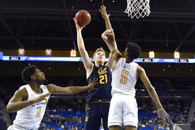 California forward Lars Thiemann, center, shoots as UCLA forward Cody Riley, left, and guard Chris Smith defend during the second half of an NCAA college basketball game Sunday, Jan. 19, 2020, in Los Angeles. UCLA won 50-40. (AP Photo/Mark J. Terrill)