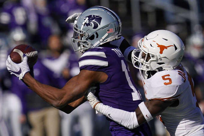 Texas defensive back D'Shawn Jamison (5) breaks up a pass intended for Kansas State wide receiver Chabastin Taylor, left, during the first half of an NCAA college football game in Manhattan, Kan., Saturday, Dec. 5, 2020. (AP Photo/Orlin Wagner)