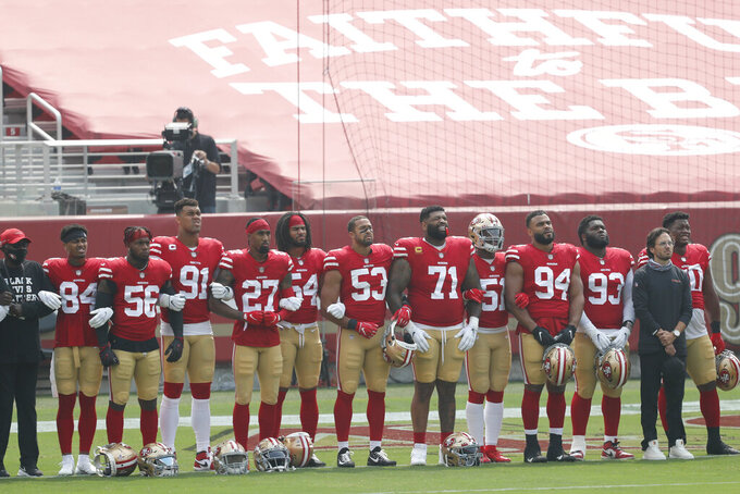 San Francisco 49ers players and coaches stand during a presentation on social justice before an NFL football game against the Arizona Cardinals in Santa Clara, Calif., Sunday, Sept. 13, 2020. (AP Photo/Josie Lepe)