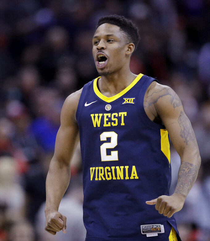 West Virginia's Brandon Knapper celebrates after making a shot during the second half of the team's NCAA college basketball game against Texas Tech in the Big 12 men's tournament Thursday, March 14, 2019, in Kansas City, Mo. West Virginia won 79-74. (AP Photo/Charlie Riedel)