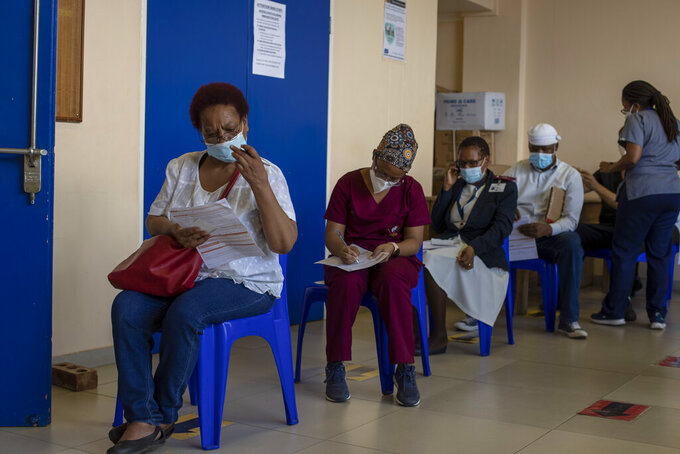 """Maggie Sedidi, left, a 59-year-old nurse at Soweto's Chris Hani Baragwanath hospital, reads a medical questioner before receiving her dose of the Johnson & Johnson COVID-19 vaccine at a vaccination center in Soweto, South Africa, Friday, March 5, 2021. Sedidi is optimistic: """"By next year, or maybe the year after, I really do hope that people will be able to begin returning to normal life."""" (AP Photo/Themba Hadebe)"""