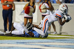 Virginia wide receiver Dontayvion Wicks (3) scores a touchdown as North Carolina defensive back Kyler McMichael (1) tackles him during the first half of an NCAA college football game in Chapel Hill, N.C., Saturday, Sept. 18, 2021. (AP Photo/Gerry Broome)