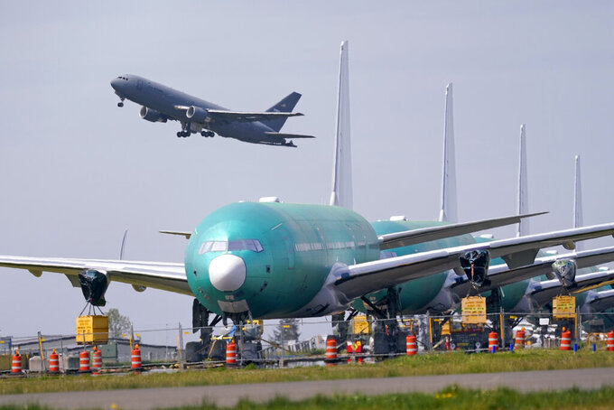 FILE - In this April 23, 2021 file photo, A U.S. Air Force KC-46A Pegasus jet takes off in view of a line of Boeing 777X jets parked nose to tail on an unused runway at Paine Field, near Boeing's massive production facility in Everett, Wash.  The Biden administration says, Monday, Sept. 13,  it will give $482 million to aviation manufacturers to help save jobs at companies that are still struggling because of the pandemic.  (AP Photo/Elaine Thompson, File)