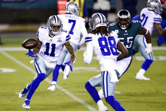 Dallas Cowboys' Cedrick Wilson (11) tosses the ball to CeeDee Lamb (88) during the first half of an NFL football game against the Philadelphia Eagles, Sunday, Nov. 1, 2020, in Philadelphia. (AP Photo/Derik Hamilton)