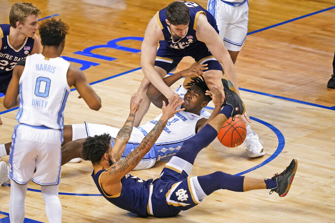 North Carolina forward Day'Ron Sharpe (11) gets tangled with Notre Dame forward Matt Zona, top, and teammate guard Prentiss Hubb, front, during the first half of an NCAA college basketball game in the second round of the Atlantic Coast Conference tournament in Greensboro, N.C., Wednesday, March 10, 2021. (AP Photo/Gerry Broome)