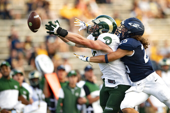 FILE - Colorado State Rams tight end Trey McBride (85) reaches for a pass while defended by Toledo Rockets safety Maxen Hook (25) during an NCAA football game on Sept. 18, 2021, in Toledo, Ohio. The player with the most receptions in college football midway through the first month is not a fleet-footed wide receiver with an NFL-bound quarterback. It's bruising Colorado State tight end McBride, who is drawing praise not only for his pass-catching, but also his blocking and leadership. (AP Photo/Emilee Chinn, File)
