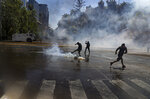 A protester kicks back tear gas fired by police trying to disperse a march against the commemoration of the discovery of the Americas, organized by indigenous groups demanding autonomy and the recovery of ancestral land in Santiago, Chile, Monday, Oct. 12, 2020. (AP Photo/Esteban Felix)
