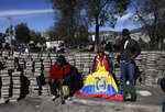 Volunteers take a break from stacking paving stones during a cleanup effort in the aftermath of violent protests against the government, in Quito, Ecuador, Monday, Oct. 14, 2019. Ecuador celebrated a deal President Lenín Moreno and indigenous leaders struck late Sunday to cancel a disputed austerity package and end nearly two weeks of protests that have paralyzed the economy and left seven dead. (AP Photo/Fernando Vergara)