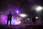 Police stand guard as Austin Fire Department put out a car fire under Interstate 35 freeway in Austin Texas, Saturday, May 30, 2020, during a protest over the death of George Floyd, a handcuffed black man who died in Minneapolis police custody on May 25.(Ricardo B. Brazziell/Austin American-Statesman via AP)