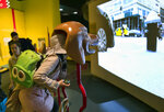 In this Tuesday, March 12, 2019 photo, a visitor takes part in an immersive experience showing visitors how dogs see from inside the head of a dog at the California Science Center in Los Angeles. A new exhibit at a Los Angeles museum examines the relationship between dogs and humans and explores why the two species seem to think so much alike and get along so well.