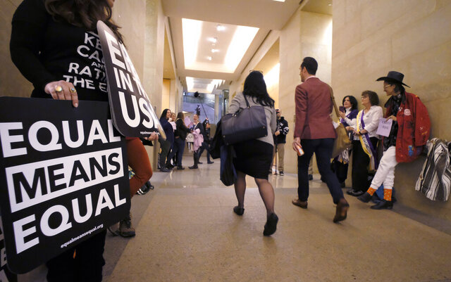 FILE - In this  Jan. 14, 2020, file photo, an Equal Rights Amendment supporters yell encouragement to two legislators as they walk down a hallway inside the state Capitol in Richmond, Va. A new poll from The Associated Press-NORC Center for Public Affairs Research shows that roughly three in four Americans support the gender equality amendment, which is now back before Congress with Virginia's ratification of the measure in January. (Bob Brown/Richmond Times-Dispatch via AP, File)