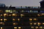 Tourists quarantined on the Diamond Princess cruise ship get some fresh air on the top deck of the ship Thursday, Feb. 13, 2020, in Yokohama, near Tokyo. Life on board the luxury cruise ship, which has dozens of cases of a new virus, can include fear, excitement and soul-crushing boredom, according to interviews by The Associated Press with passengers and a stream of tweets and YouTube videos. (AP Photo/Jae C. Hong)