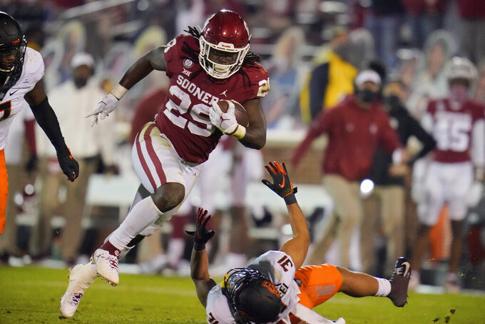 Oklahoma running back Rhamondre Stevenson (29) carries past Oklahoma State safety Kolby Harvell-Peel (31) during the second half of an NCAA college football game in Norman, Okla., Saturday, Nov. 21, 2020. (AP Photo/Sue Ogrocki)