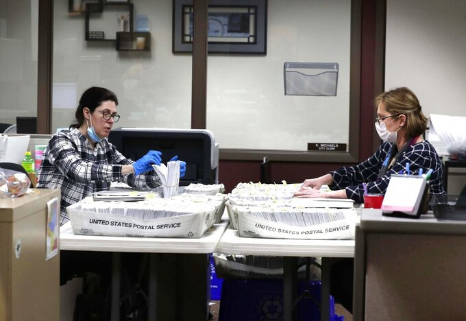 From left Katherine Katsekes, and Diane Scott, both paid volunteers, help sort absentee ballots by ward to be opened on election day at Brookfield City Hall, Tuesday, March 31, 2020. Many area communities are having a steady stream of residents voting early as concerns about the coronavirus raise questions about the upcoming April 7 election. (Rick Wood/Milwaukee Journal-Sentinel via AP)