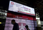 People wearing face masks walk past a bank's electronic board showing the Hong Kong share index at Hong Kong Stock Exchange Monday, July 6, 2020. Asian stock markets rose Monday as investors looked ahead for data they hope will support optimism about a global economic recovery. (AP Photo/Vincent Yu)