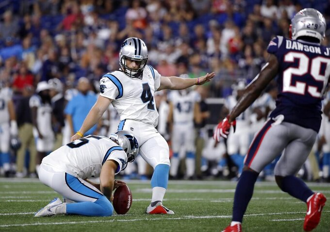 FILE - In this Aug. 22, 2019, file photo, Carolina Panthers kicker Joey Slye (4) kicks against the New England Patriots in the second half of an NFL preseason football game in Foxborough, Mass.  The Panthers brought kicker Joey Slye to training camp on a whim, someone to be a camp body and give Graham Gano a rest when needed. But with Gano on IR, Slye, an undrafted rookie and virtual underdog, has won the job and will handle kicking duties this season for Carolina.(AP Photo/Elise Amendola)