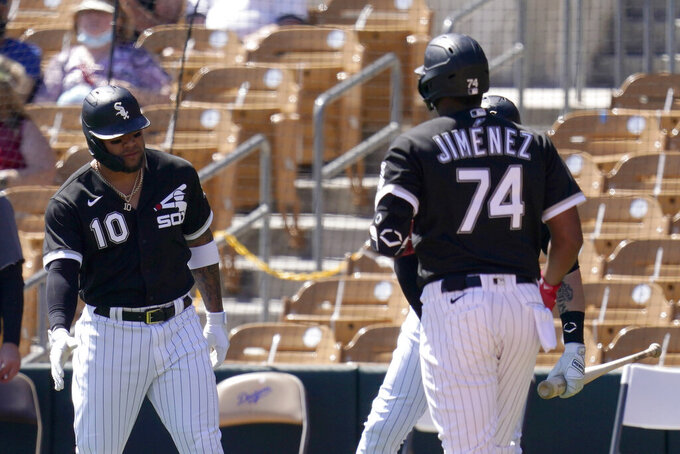 Chicago White Sox's Eloy Jimenez (74) celebrates his two-run home run against the San Francisco Giants with Yoan Moncada (10) during the first inning of a spring training baseball game Monday, March 22, 2021, in Phoenix. (AP Photo/Ross D. Franklin)