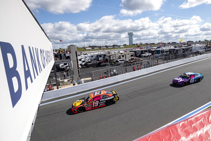 Martin Truex Jr. (19) and Alex Bowman (48) compete during a NASCAR Cup Series auto racing race at Charlotte Motor Speedway, Monday, Oct. 11, 2021, in Concord, N.C. (AP Photo/Matt Kelley)
